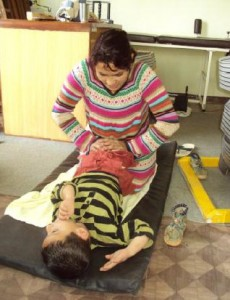 Ganga, manager helping a patient with physio